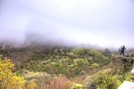 thundershower: Greece. Fog. The scenic Meteora Rocks. Girl photographs on the brink precipice