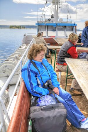 ONEGA  LAKE, RUSSIA - August 10.2008: Woman with camera on the top deck of the pleasure boat looking into the distance