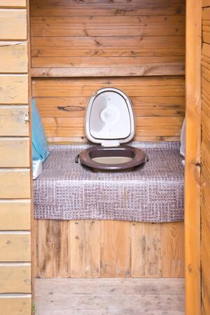 Rustic toilet cubicle with a slop bucket
