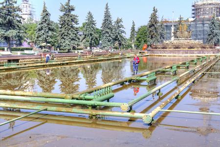 MOSKOU, RUSLAND - Mei 28 2014: Tentoonstelling van prestaties van de People's Economy (VDNKh). Werknemers produceren schoonmaak en reparatie van pijpen van de fontein de steen bloem