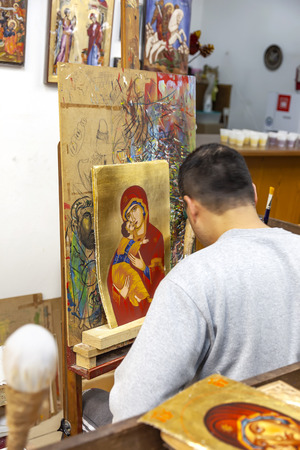 METEORA, GREECE - March 13.2016: The temple complex. Icon painting studio. The master icon painter writes an icon Editorial