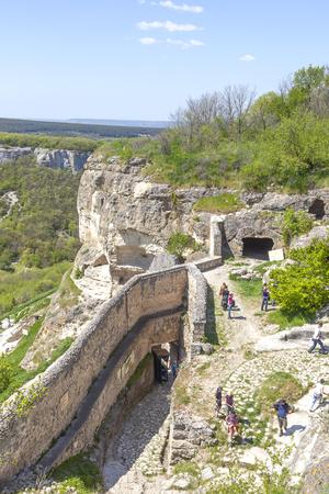 CHUFUT-KALE, CRIMEA, UKRAINE - May 02.2010: People on ruins of medieval spelaean site of ancient settlement