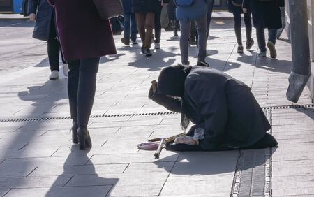 Beggar begs for alms at passersby kneeling Stock Photo