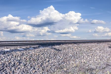 Collage. Railroad against the background of cumulus clouds