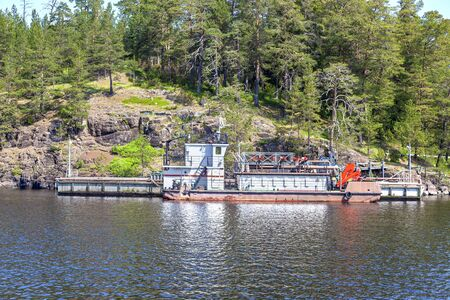 Monastic bay on the island of Valaam. Cargo barge at the cargo pier