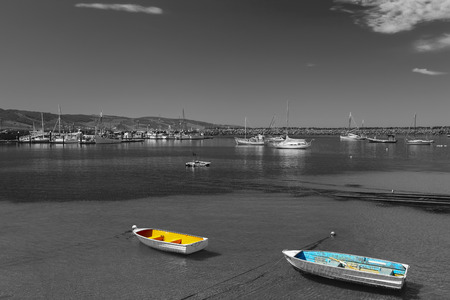 dingy: A Yellow and White Dingy with a Blue and White Dingy.This is a Black and White Image with Just these tow Boats Hilighted in full Color.Image is Taken at Apollo Bay on the Great Ocean Road in Victoria Australia.