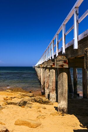 lonsdale: Striking image of the Jetty at Point Lonsdale.The Jetty is made of Timber over Golden Sand and Green Sea under a Blue Sky.Point Lonsdale is Located near Melbourne and Geelong in Victoria Australia.