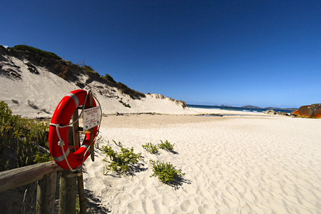 Red Lifesaving Ring at the Begining of a Sandy Beach under Blue Sky.Sand Hills on one Side and Red Rocks on the other.This is Located at Squeaky Beach in Wilsons Promatory at the Bottom of Victoria in Australia Stock Photo