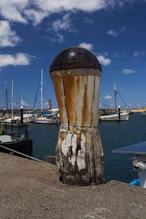 great bay: Weathered Timber Bollard with a Steel Cap that is Rusted and causing Rust stains to run down the White Bollard.Boats and the Bay of Apollo Bay on the Great Ocean Road in Victoria, Australia