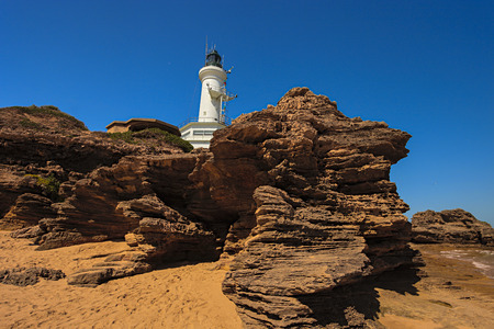 lonsdale: Photo of the Point Lonsdale Lighthouse taken from the Beach showing the Rocks below the Lighthouse.Point Lonsdale is Located in Victoria Australia. Stock Photo