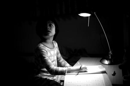 Retrato monocromo de niñas asiáticas haciendo sus deberes bajo la lámpara de iluminación en una habitación oscura Foto de archivo