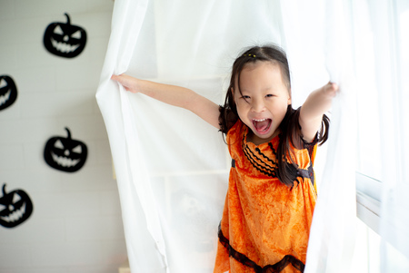 Portrait Asian little girl playing and hiding in the white clean curtain with Halloween decoration in background. Stock Photo