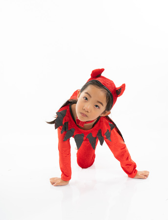 Portrait Asian little cute girl in evil costume for Halloween festival with pumpkin