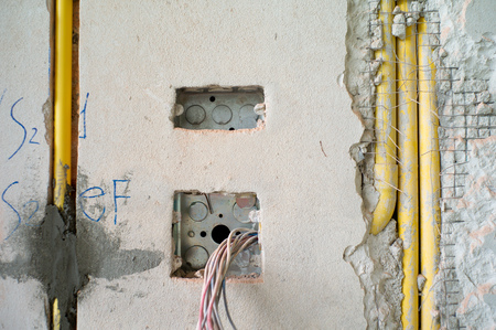 Abstract texture and background of electrical system under installation inside the concrete wall in the house under construction.
