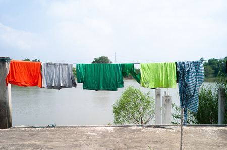 Old wet clothes hanging on the clothsline with blue sky and river in background