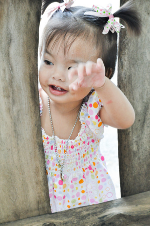 Portrait Asian little girl with smiling face plays at the outdoor with silver necklace of passed away king Rama nine of Thailand