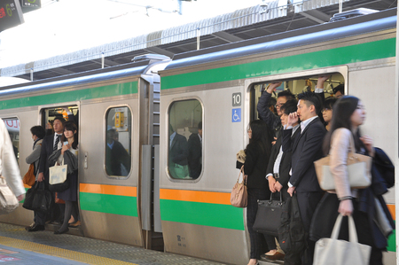 Tokyo, Japan:November 13, 2014 -  The crowd of passengers traveling by the train during rush hours in Tokyo, Japan. Crowded people in the platform of JR station