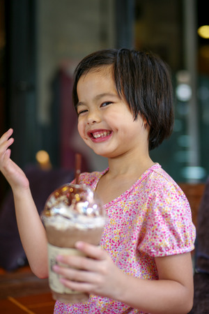 Portriat Asian little girl drinking blended ice chocolate with funny face. Happy girl enjoy eating soft drink with big smile and dimples on cheek at the cafe Stock Photo