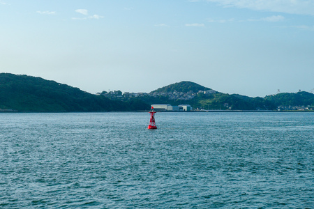 Red buoy floating in the sea with seascape and landsacpe in background. The ship traveling along the ocean with cityscape and cable bridge in background