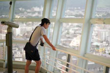 Portrait Asian man looking the city view from the high tower, Beppu tower, in Japan