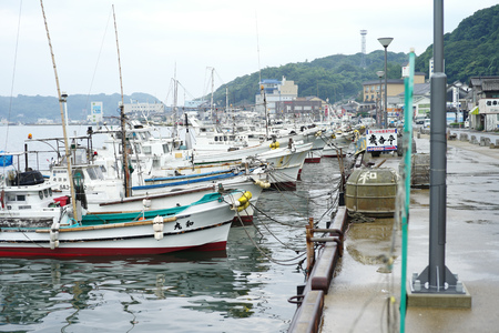 Saga, Japan:September 1, 2016 - Landscape with group of fishing boat parking at the port with cityscape in background. Traditional occupation of Japanese people in Saga city Archivio Fotografico - 123677909