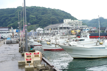 Saga, Japan:September 1, 2016 - Landscape with group of fishing boat parking at the port with cityscape in background. Traditional occupation of Japanese people in Saga city Archivio Fotografico - 123677910