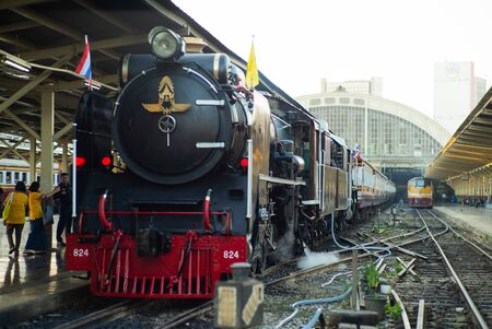 Bangkok,Thailand:December 5, 2018 - Closeup vintage steam train parking at the station waiting for departing. Crowd of people taking the picture with the train locomotive