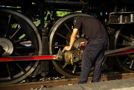Closeup worker dropping the lubricant oil into the steel wheel of vintage train locomotive. Repair and maintenance concept