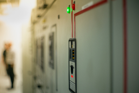 Closeup lighting indicator on the control carbinet in the electrical room with blurred electrician in background