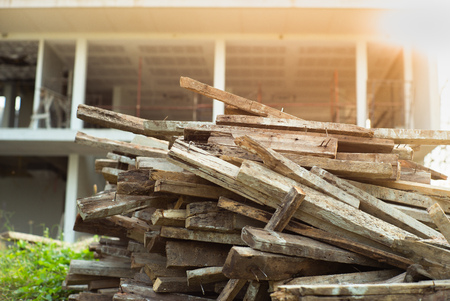 Closeup pile of wood with blurred house under construction in background Reklamní fotografie