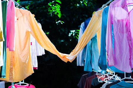 Colorful wet clothes hanging on the steel clothesline for drying by the heat of sun. Sweet couple of shirts concept. Happy valentines day Stok Fotoğraf