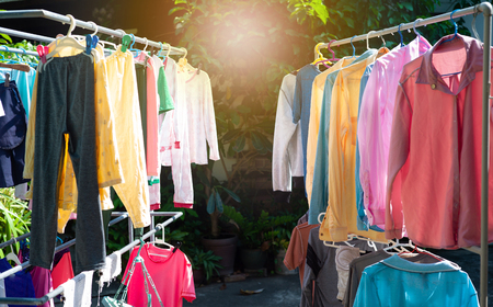Colorful wet clothes hanging on the steel clothesline for drying by the heat of sun