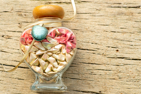 Top view of glass jar with folding paper in shape of little heart inside. Craftsmanship of folding paper for gift in Valentines day occasion. Standard-Bild