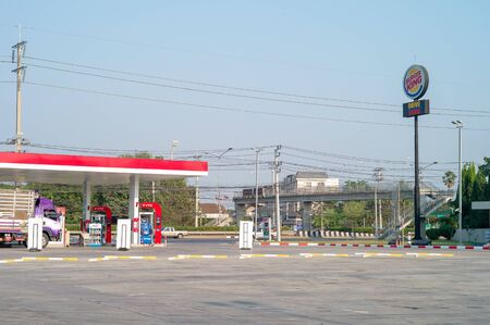 Nakhonpratom, Thailand : January 27, 2019 - Landscape oil station with steel pole of drive through service. Sign of Burger King drive through service. Rest area for vehicle near high way road.