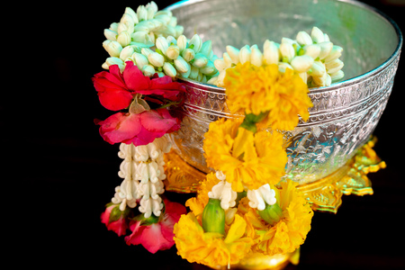 Isolated closeup flower garlands hanging on the edge of silver bowl with black background