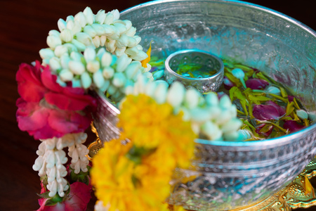Closeup flower garlands hanging on the edge of silver bowl with flower petal floating on the water in background