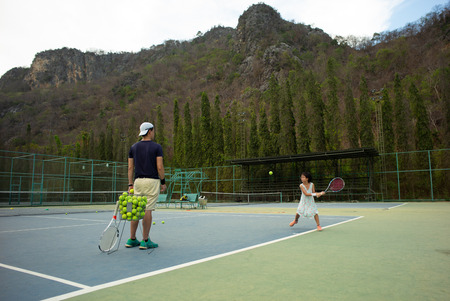 Portrait Asian girl plays tennis with her father and coach at outdoor court with stone mountain and forest background Archivio Fotografico
