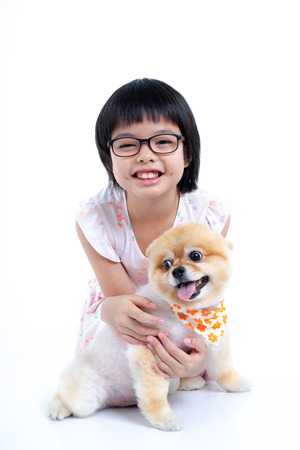 Isolated portrait Asian little girl holding Pomeranian dog with care on white background. Studio shot of girl and puppy Archivio Fotografico - 123720499