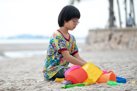 Portrait Asian girl with eyeglasses builds the sand castle on the beach by colorful models Archivio Fotografico - 123720509