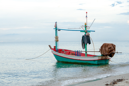Small traditional fishing boat floating in the sea at coast with calm surface on ocean and clouded sky Archivio Fotografico - 123720513