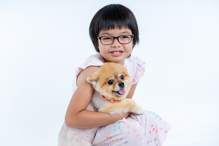 Isolated portrait Asian little girl holding Pomeranian dog with care on white background. Studio shot of girl and puppy Archivio Fotografico - 123720549