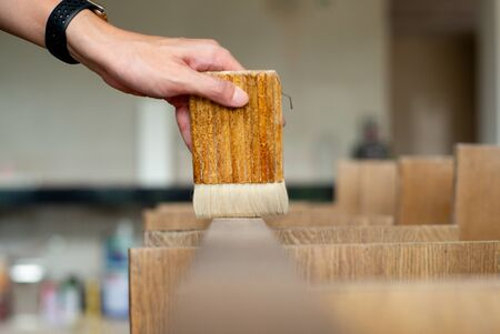 Selective focus on a hand of carpenter holds a wooden paint brush and applies on the wood surface at the construction site Archivio Fotografico - 126645777