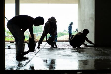 Silhouette group of workers build the cement floor in the house under construction. Stockfoto
