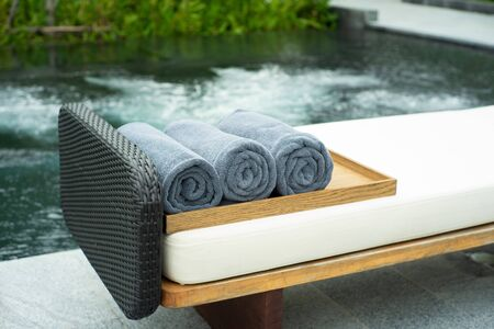 Closeup rolls of towel on the wooden tray on beach bed with blurred bubble of whirlpool in background. Spa industry