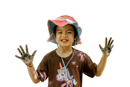 Portrait of Asian little girl enjoys playing in the farm. Smiling girl shows her dirty hands after molding the mud.