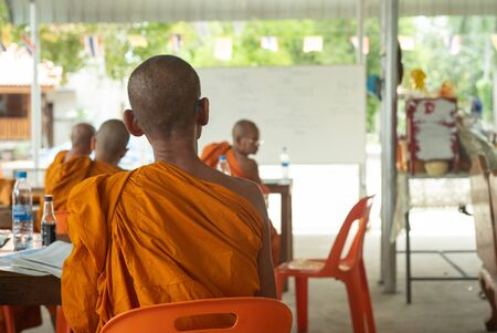 Back portrait of monk sits in the class at the temple with blurred group of monks in background