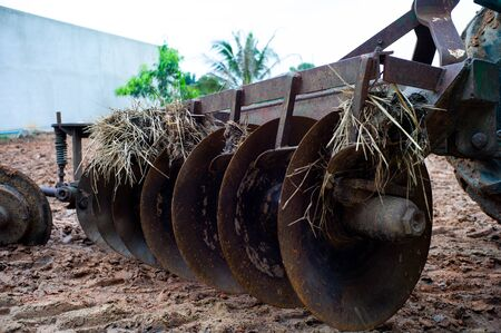 Closeup disk harrows on the back of tractor. Dirty steel blades of tractor with dried straw and soil Stok Fotoğraf