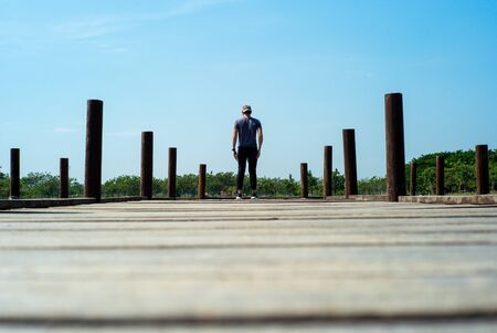 Back portrait of handsome man in casual cloth stands on wooden bridge with blue sky background