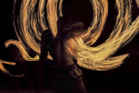 Motion blurred portrait of man dances with fire on the beach with dark night background Stockfoto