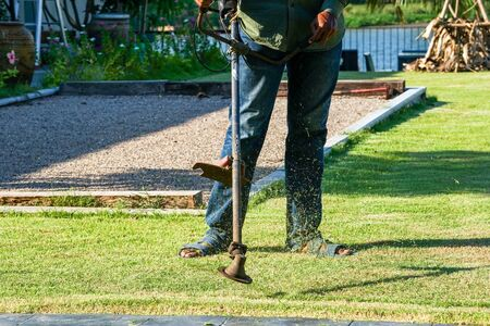 Closeup legs of gardener mows the grass in the outdoor garden with mowing tool in sunny day